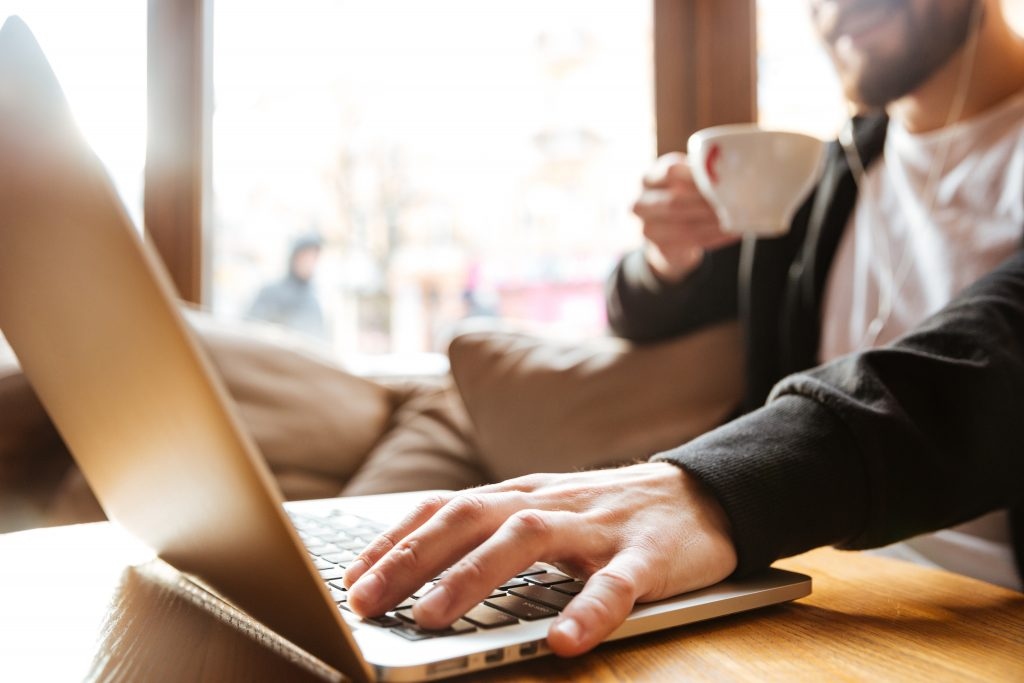 A person placing one hand on a laptop and holding the cup in the other hand